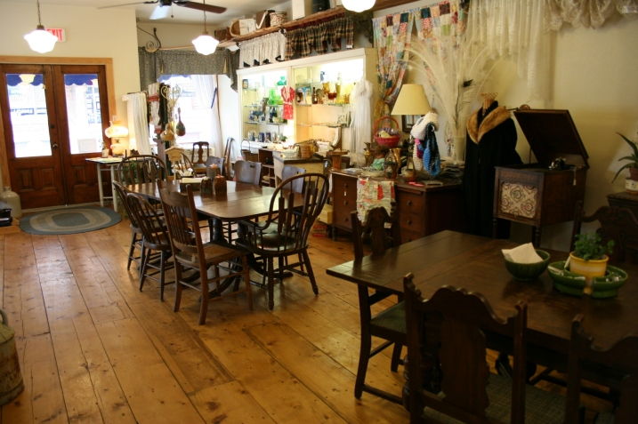Shoppers can relax with a cup at a table and then buy the table and chairs if they wish. Note the beautiful wood floor, which is not original to the store. LaNette bought some pine planks at the lumberyard to recreate the vintage look.