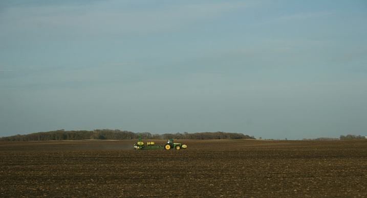 As the sun begins to set along Minnesota Highway 15, a John Deere works the land.