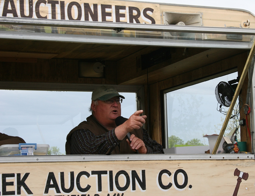 The auctioneer solicits bids from his movable auction wagon.