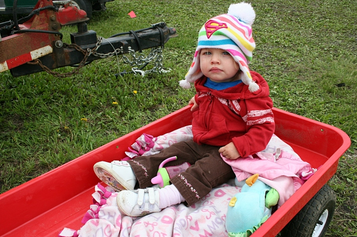 Eighteen-month-old Marina, bundled up and riding in a wagon pulled by her dad.
