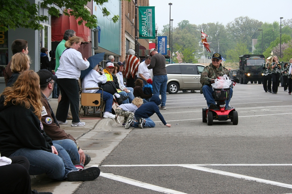 A vet on a motorized scooter tossed candy to the kids.