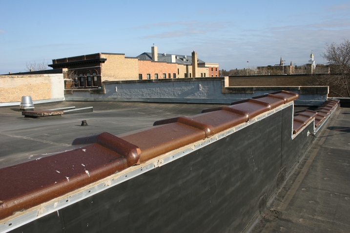 On the left, a low wall separates the printing business rooftop from the theatre roof.