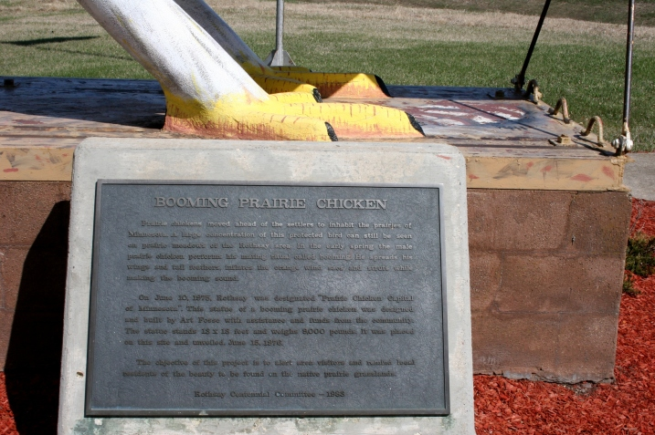 The feet of the giant prairie chicken along with info about the statue built in 1976 by artist
