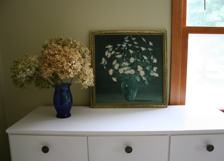 In the guest bedroom, I created this floral scene atop a dresser. The floral print came from a garage sale, bought for under $1. I seldom spend much on any art I buy. The hydrangea are from my frontyard bush and the vase from flowers I once received.