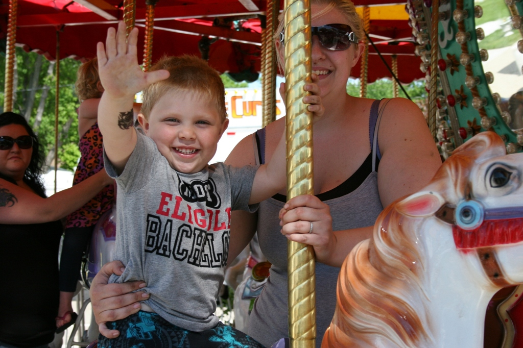 Dakota waves to his dad who is photographing his little boy's ride on the merry-go-round.