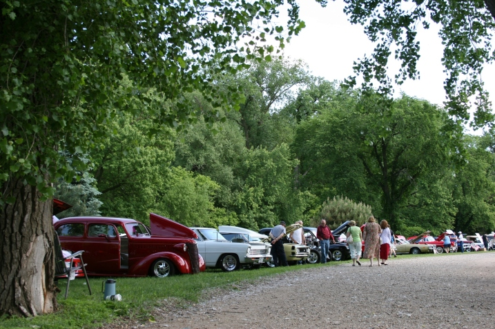 Vintage vehicles line the grassy banks of the Straight River in TeePee Tonka Park, Faribault.