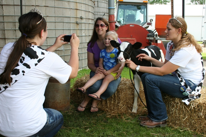Rice County Dairy Princess Tracie Korbel takes photos while Dairy Princess Kaylee Wegner tends the calf.