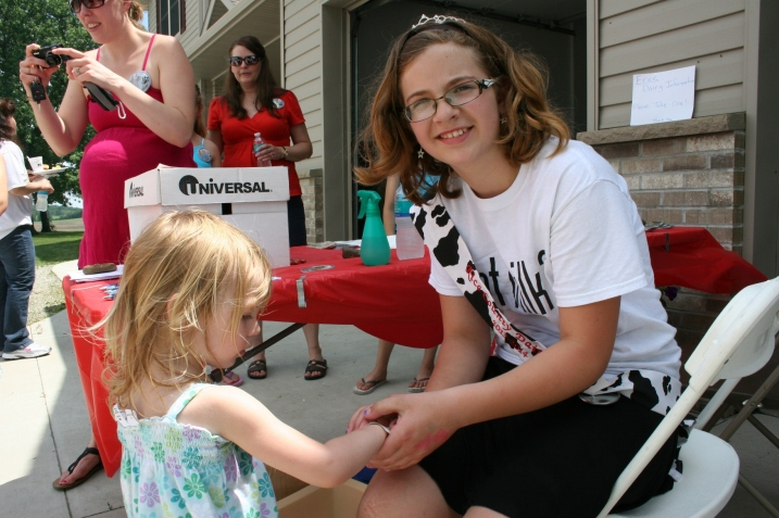 Rice County Dairy Maid Kelsey Kuball applied temporary tattoos.