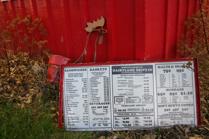 A vintage menu is propped outside the restaurant.