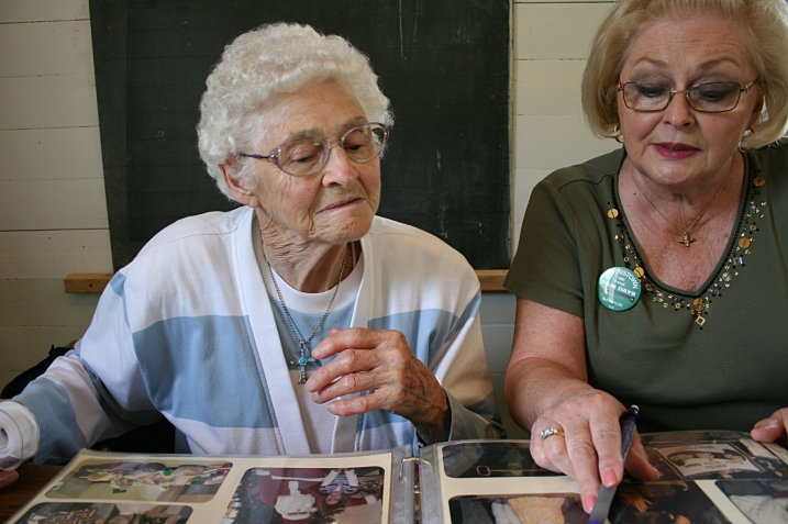 Helen and Cindy visit while they cut and tape information into the album.