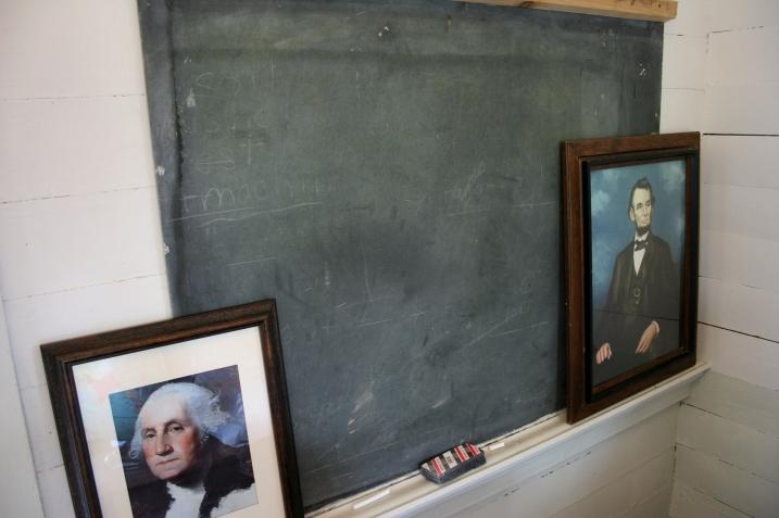 Presidential portraits grace the blackboard by the teacher's desk.