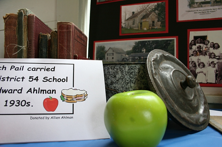 A display of school-related items includes a lunch pail.