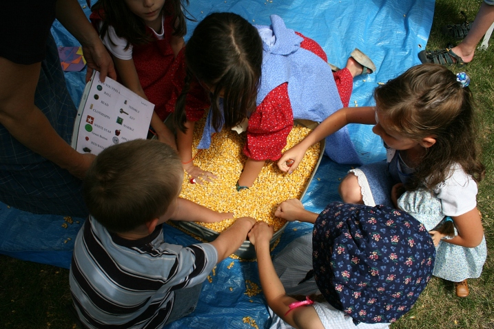 Kids, including my niece, right, dig for objects in a tub of corn.