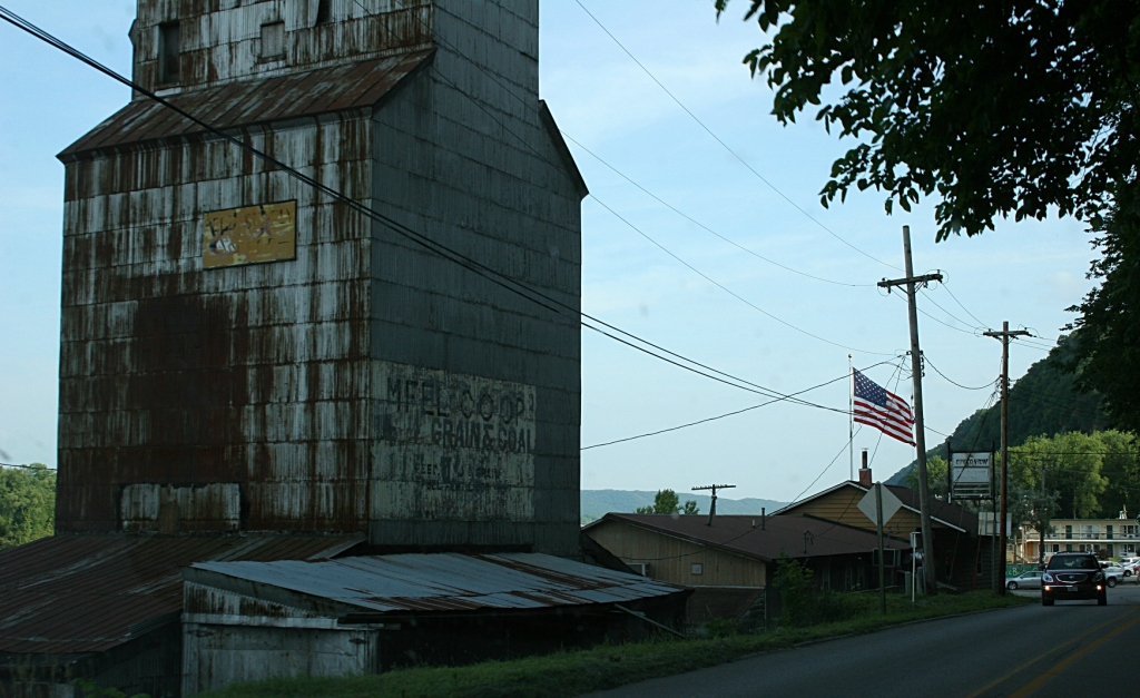 Snapped through the windshield of the van, this aged elevator and flag to the right, entering the Mississippi River town of Marquette, Iowa, from the north.