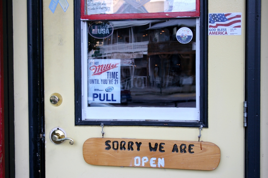 """A few miles to the south in McGregor, Iowa, I found this """"God bless America"""" sticker and humorous welcome on the door of a bar."""