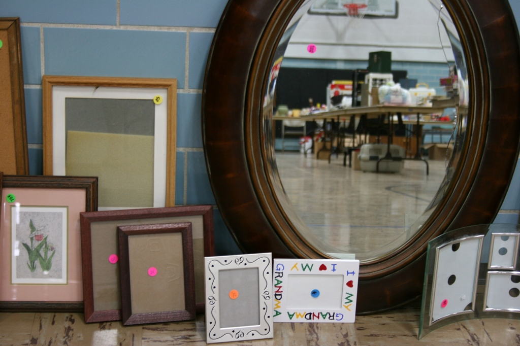 Frames and mirrors and merchandise reflected.