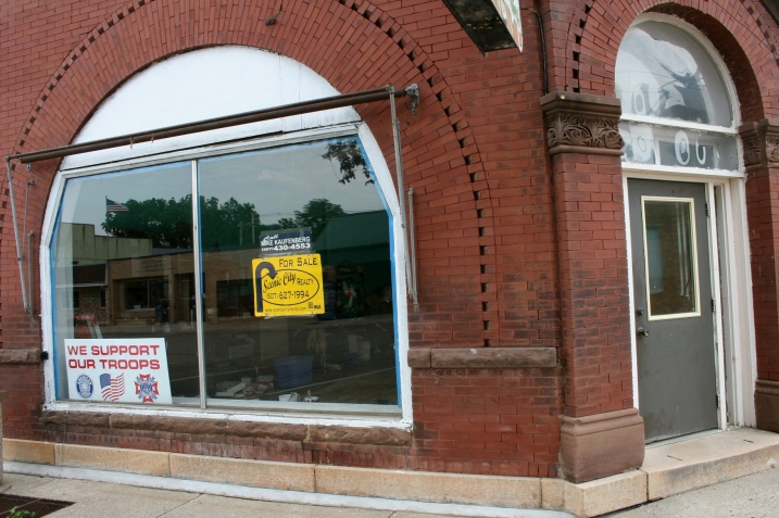 The yellow sign in the front window advertises the property for sale through Scenic City Realty.