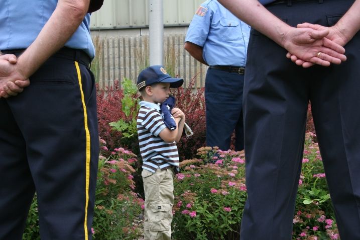 Young Carter hugs the American flag, which he accepted in honor of his military family.