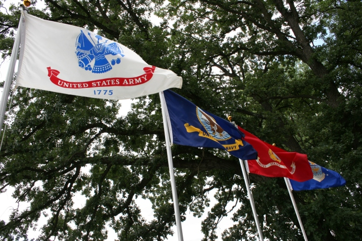 Flags from the four branches of the military fly next to Geri Larson's cabin.
