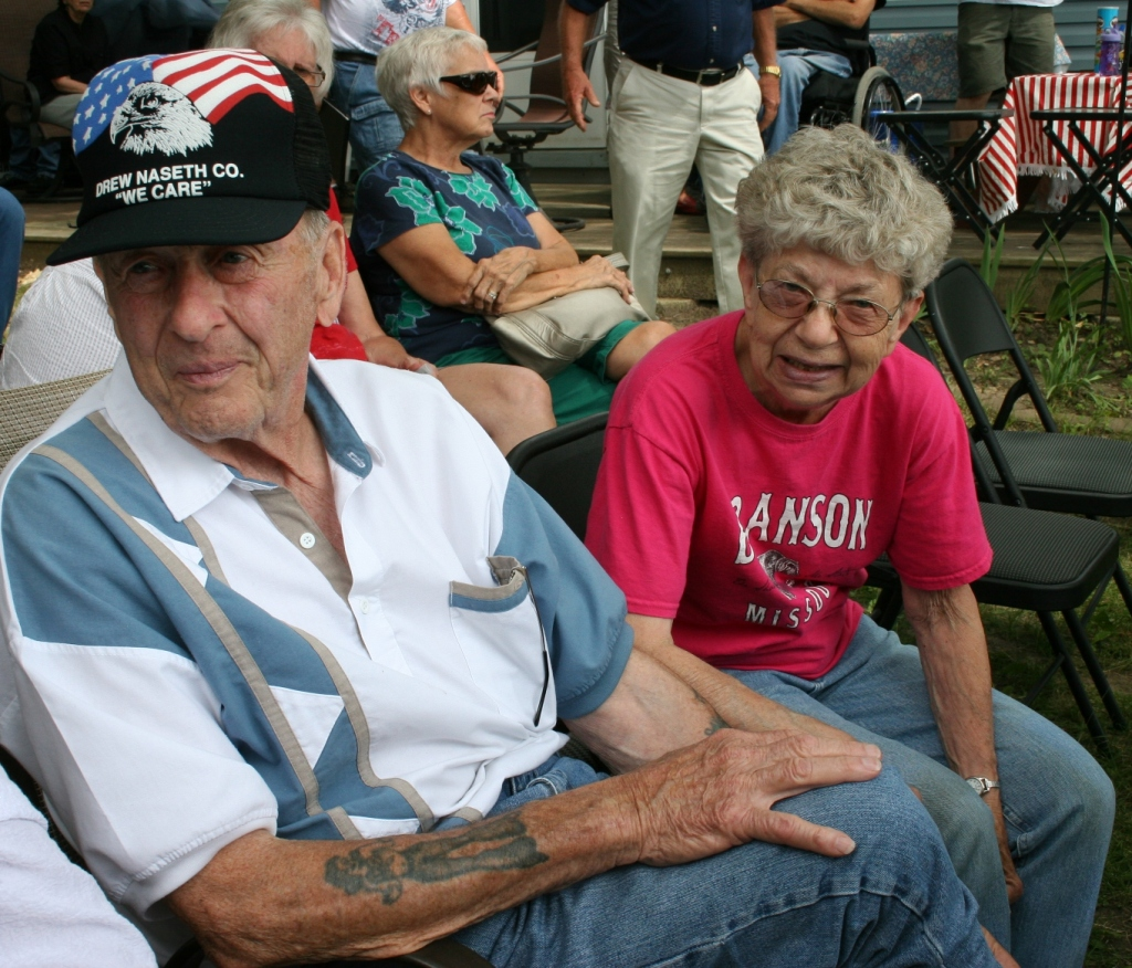 Geri Larson with her friend, George LaRoche, who installed the poles for the military flags on her property.