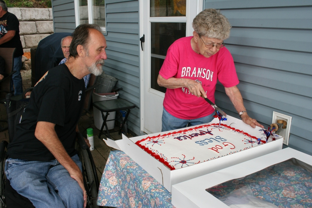 Geri Larson prepares to slice the cake, served along with sandwiches and beverages, after the dedication ceremony.