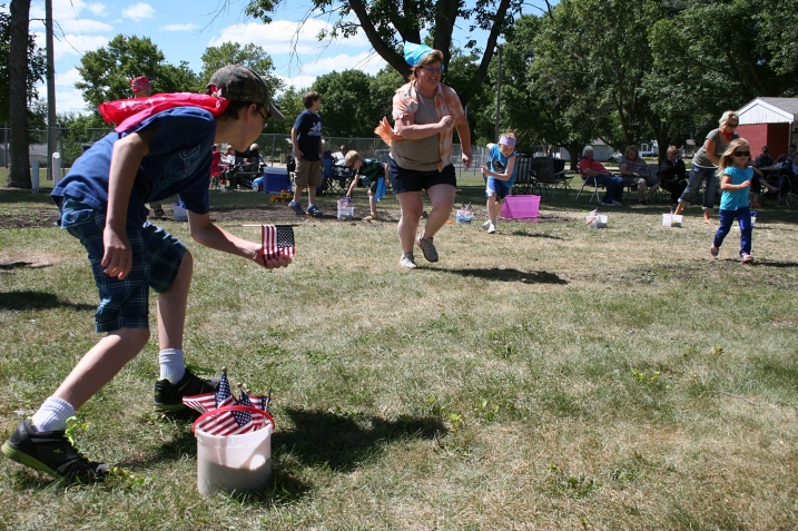 In the flag race, contestants carry flags from one ice cream bucket to another.