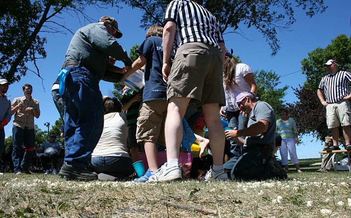 Referees watch over the competition in which contestants filled cups, attached to their feet, with popcorn and raced to fill ice cream buckets.