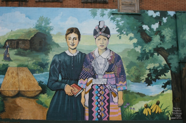 This snippet of the mural shows Laura Ingalls Wilder as a teacher next to a Hmong woman. To the left is the log bridge spanning Plum Creek, where the Ingalls family lived in a dug out.