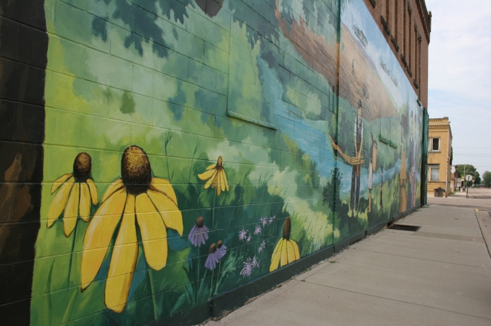 Native prairie plants, like black-eyed Susan and coneflowers, are part of the painting.