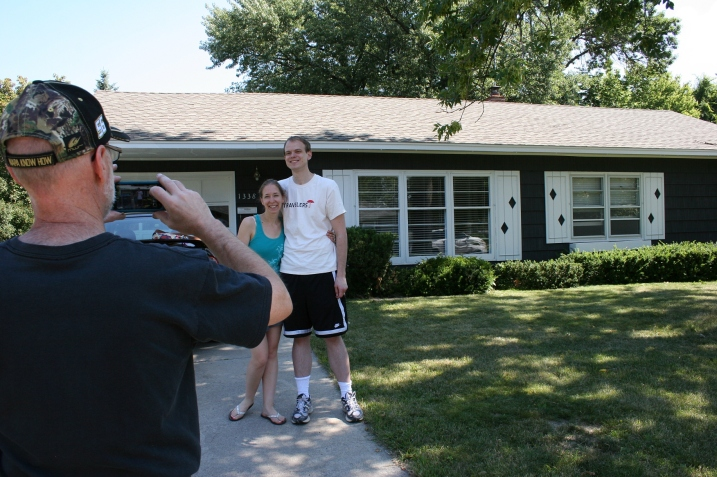 My husband photographs our eldest daughter and her fiance in front of the rental house that will soon be their new home.