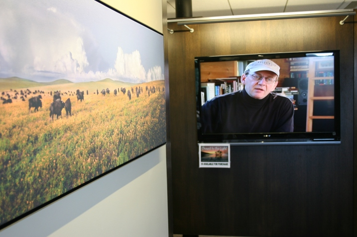 A Brandenburg bison photo hangs to the left and the photographer talks about his work in a video, right.