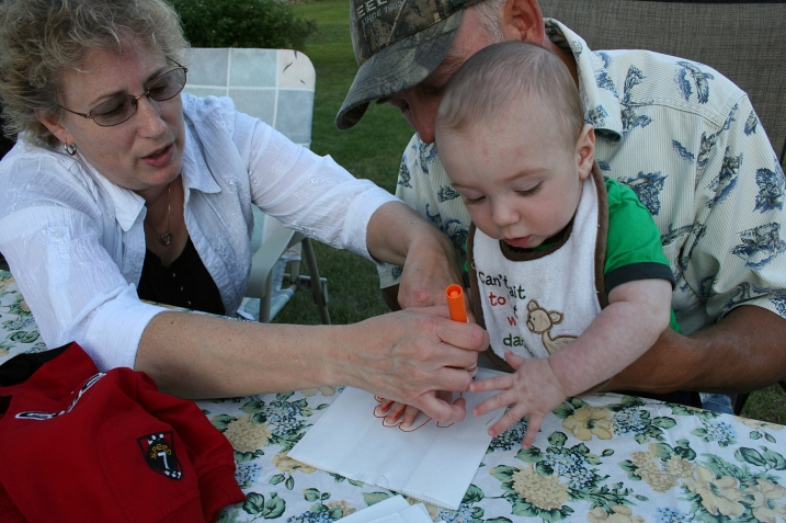 Grandma Cheryl and Grandpa Roger help 6-month-old Aston make a luminary.