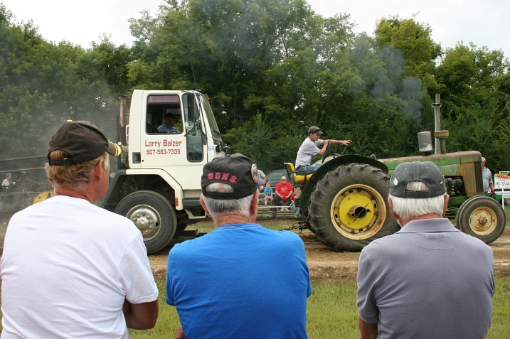 The wheels on the tractor go round and round at the tractor pull.