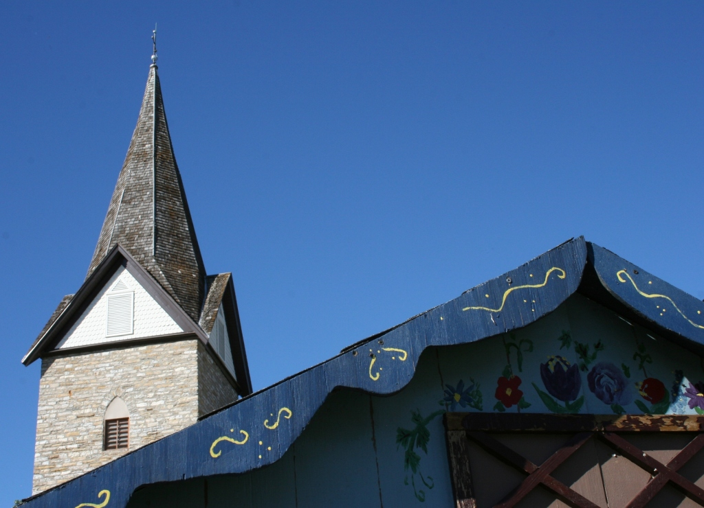 The steeple of the historic stone church with the roofline of a German themed beverage booth in the foreground.