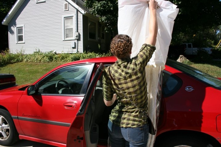 Miranda carefully lifts the beaded replica vintage bridal gown for placement inside her car.