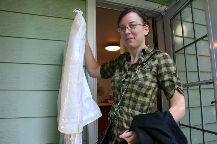 The maid-of-honor, my daughter Miranda, carries her sister's wedding gown to her car.