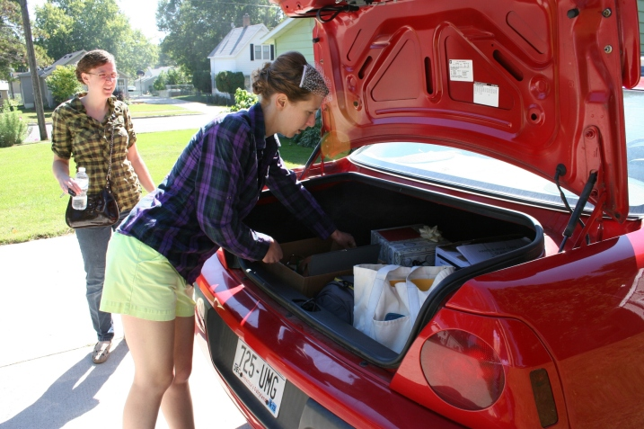 The sisters, my daughters, load wedding item necessities and Amber's belongings into the car. They joked about their plaid shirts.