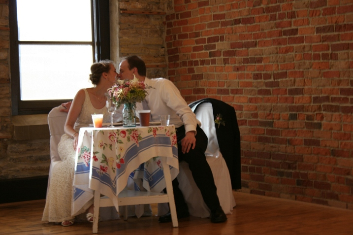 A sweet kiss at their wedding reception sweetheart table set just for them.