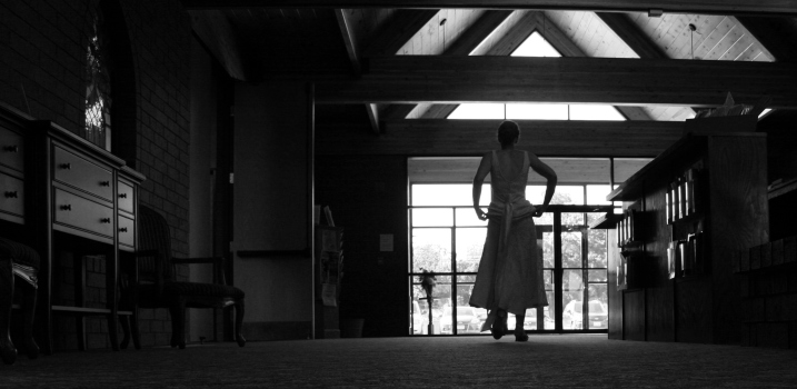 The bride lifts up her dress as she walks through the narthex.