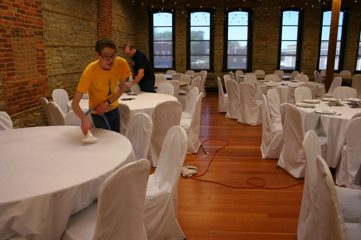 The bride's brother, Caleb, steam presses tablecloths while the father-of-the-groom, Eric, works on setting tables.