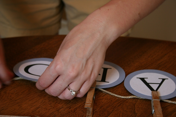 Card gift boxes, in my opinion, are not exactly original. So the bride and I came up with an idea that was simple and vintage and personal. Here Amber attaches CARDS letters to jute with clothespins from my clothespin bag.