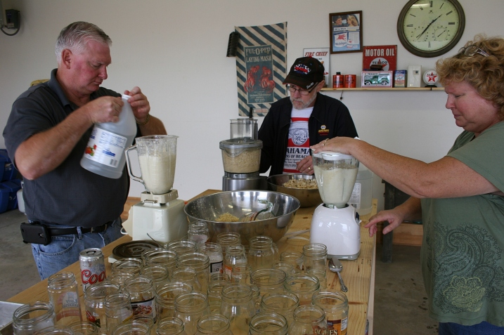 Brian, left, and Lanae blend the horseradish with vinegar in blenders while Randy uses the food processor.