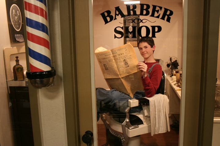 Noah, who volunteers at the library through its youth program, sat in the museum's barbershop chair during A Night at the Museum. in the museum barbershop.
