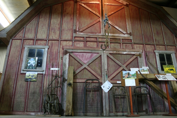 A barn front forms a backdrop in Harvest Hall, where visitors can learn about the area's agricultural heritage.
