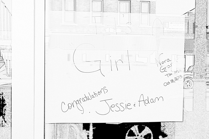 A birth announcement in the front window of a downtown business, converted to black-and-white so it's readable.