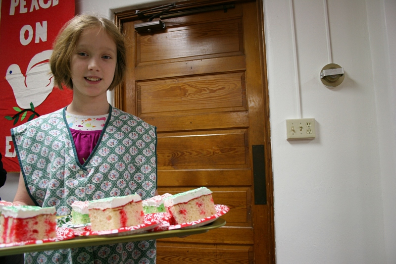 Volunteer Madeline serves Christmas cake at a past dinner. Minnesota Prairie Roots file photo 2013.
