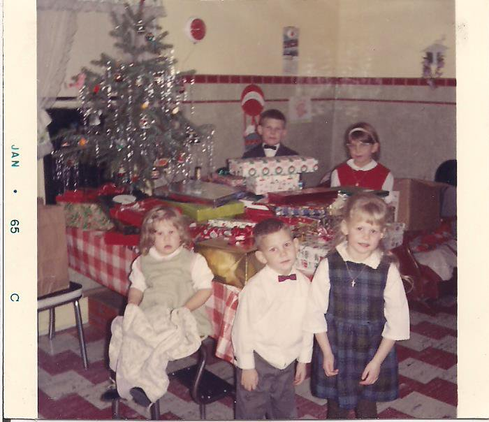 Our family Christmas tree always sat on the end of the kitchen table, as shown in this Christmas 1964 photo. That's me in the red jumper with four of my five siblings.