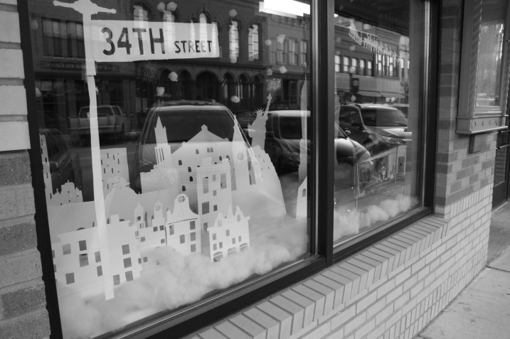 An artistic interpretation of Miracle on 34th Street graces a front window at the Paradise Center for the Arts, which reflects some of downtown Faribault's historic buildings.