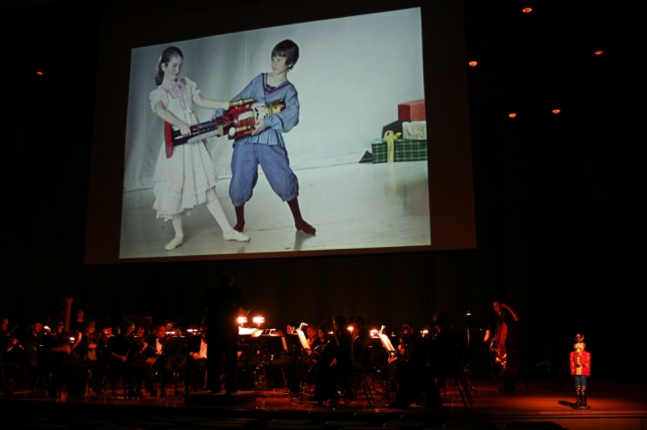 Versions of the Nutcracker play on screen while the orchestra performs.