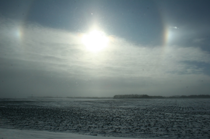 Sun dogs photographed through the dirty passenger side window of the van this morning east of Lamberton along U.S. Highway 14.